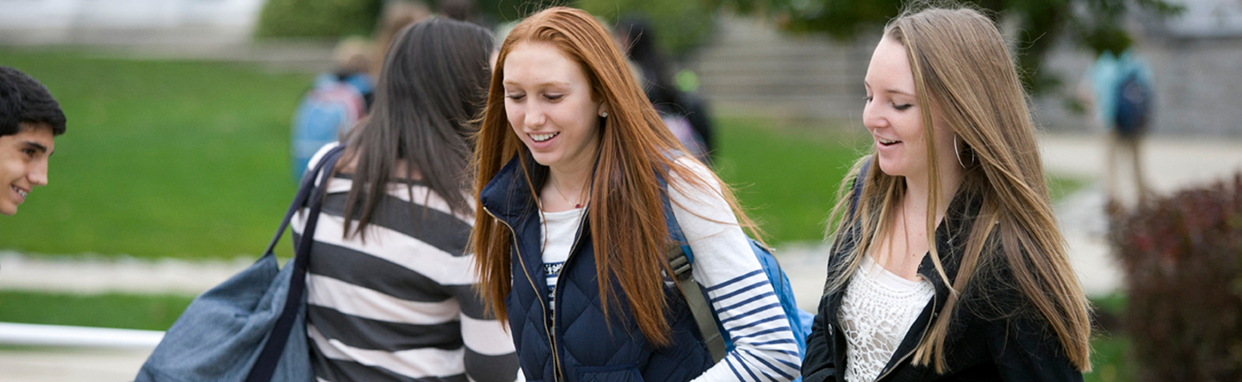 Two female students talking as they walk to class