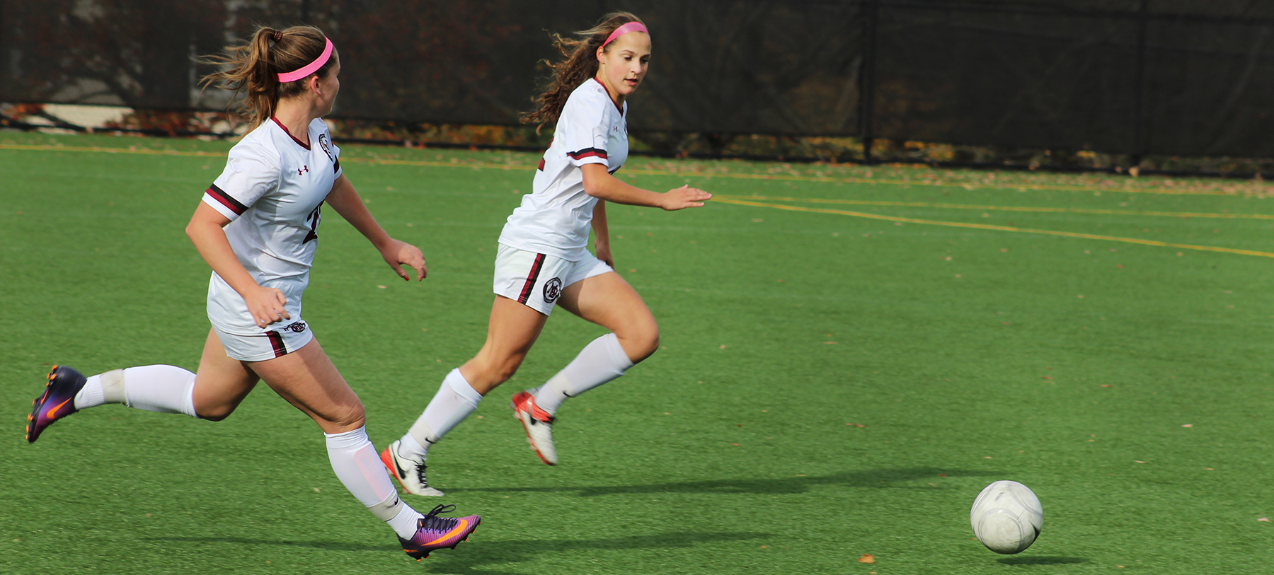 Two girls in soccer uniforms run while kicking a ball